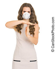 Young woman in mask showing stop gesture