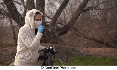 Young woman in medical mask and gloves coughing, holding on to rudder of bicycle in countryside. Female protecting yourself from diseases on walk. Concept of threat of coronavirus epidemic infection.