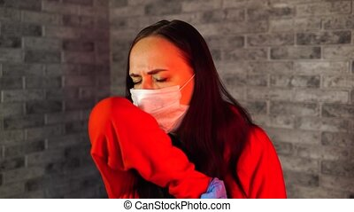 Young woman in medical mask and gloves coughing in elbow, being isolated at home. Adult female protecting yourself from diseases. Concept of threat of coronavirus epidemic infection.