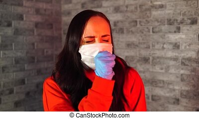 Young woman in medical mask and gloves coughing into fist, being isolated at home. Adult female protecting yourself from diseases. Concept of threat of coronavirus epidemic infection.