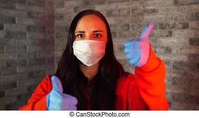 Young woman in medical mask and gloves showing thumbs up, being isolated at home. Adult female protecting yourself from diseases. Concept of threat of coronavirus epidemic infection.
