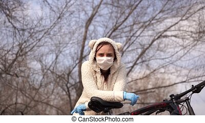 Young woman in medical mask and gloves stands, leaning on bicycle in countryside. Female protecting yourself from diseases on walk. Concept of threat of coronavirus epidemic infection.