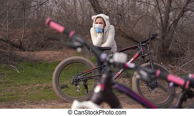 Young woman in medical mask and gloves stands, leaning on ...