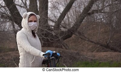 Young woman in medical mask and gloves stands with bicycle, holding on to rudder in countryside. Female protecting yourself from diseases on walk. Concept of threat of coronavirus epidemic infection.