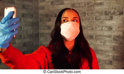 Young woman in medical mask and gloves taking selfie on ...