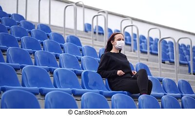 Young woman in medical mask looks away, sitting on stadium bleachers alone. Adult female in black casual clothes protecting yourself from diseases. Concept of threat of coronavirus epidemic infection