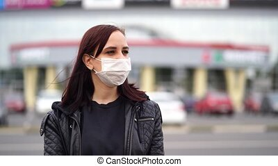 Young woman in medical mask looks away, standing on street in city. Close up of female protecting yourself from diseases on walk. Concept of threat of coronavirus epidemic infection