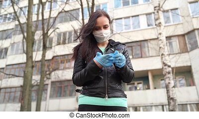 Young woman in medical mask putting on medical gloves on street. Close up of female protecting yourself from diseases on walk. Concept of threat of coronavirus epidemic infection.