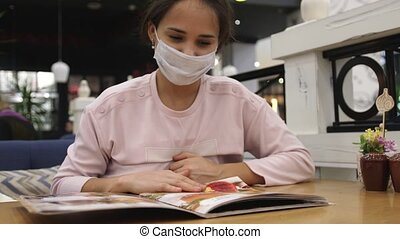 Young woman in medical mask sitting at the table at cafe or ...