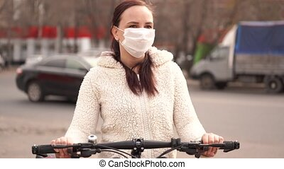 Young woman in medical mask stands with bicycle in city ...