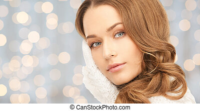young woman in mitten over blue lights - winter holidays,...