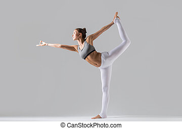 Young woman in Natarajasana pose, grey studio background