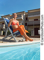 young woman in orange bikini and pareo sitting on beach chair near pool and smiling, house