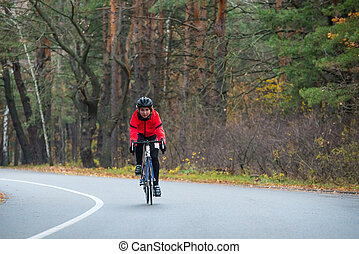 Young Woman in Orange Jacket Riding Road Bicycle in the Park in the Cold Autumn Day. Healthy Lifestyle.