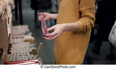 Young woman in orange sweater chooses wrapping paper Christmas decor.