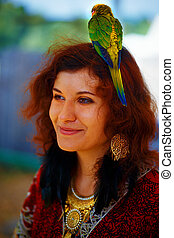 Young woman in ornamental dress and beautiful gold jewelry with a color parrots in hair.
