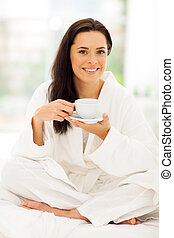 young woman in pajamas drinking coffee