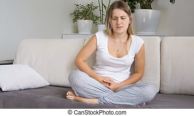 Young woman in pajamas sitting on sofa and suffering from menstrual pain