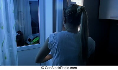 Young woman in pajamas sneaking in refrigerator at night and taking food at night