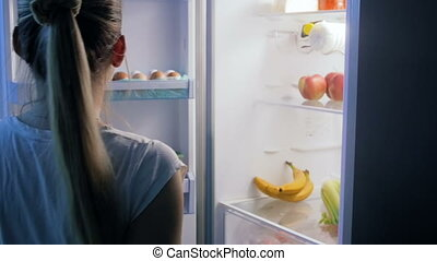 Young woman in pajamas taking fresh banana from refrigerator at night