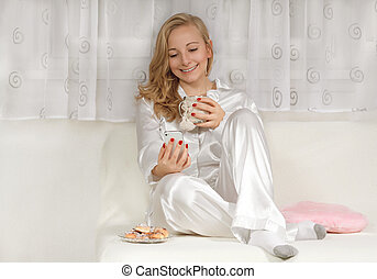 Young woman in pajamas using smartphone on bed