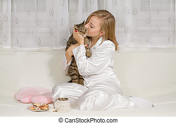 Young woman in pajamas with a cat