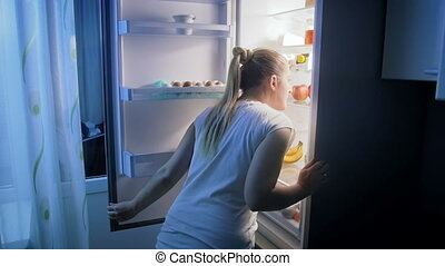 Young woman in pajams opens refrigerator at night and looking for food