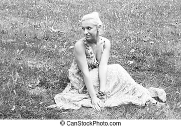 Young woman in park sitting on grass