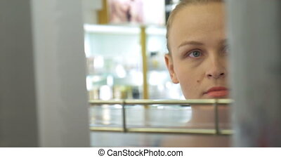 Young Woman in Perfumery Shop - Closeup shot of a young...