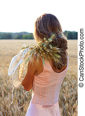 Young woman in pink dress holding wheat ears and hat in her hands