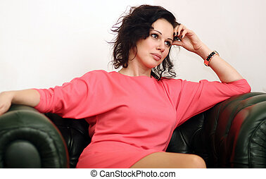 woman in  pink dress sitting on green sofa