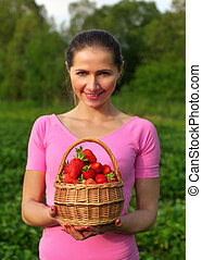 Young woman in pink holding basket full of strawberries just picked from the field behind her. Shallow depth of field - focus on strawberry only