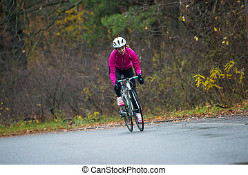 Young Woman in Pink Jacket Riding Road Bicycle in the Park in the Cold Autumn Day. Healthy Lifestyle.