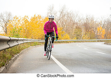 Young Woman in Pink Jacket Riding Road Bicycle on the Highway in the Cold Autumn Day. Healthy Lifestyle.