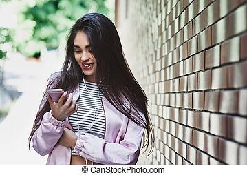 Young woman in pink jacket standing near wall listening music in