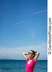 Young woman in pink shirt standing by the sea