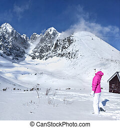 Young woman in pink ski jacket, gloves, hat looking at the top of snow covered Lomnicky stit peak, shading her eyes with hand on a sunny day. Skalnate sedlo ski resort, Slovakia.