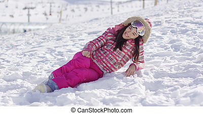 Young woman in pink snowsuit with ski goggles