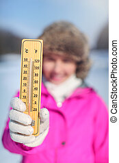 Young woman in pink sport jacket holding wooden thermometer outside on cold day, illustrating weather with temperature as low as -20 degrees Celsius.
