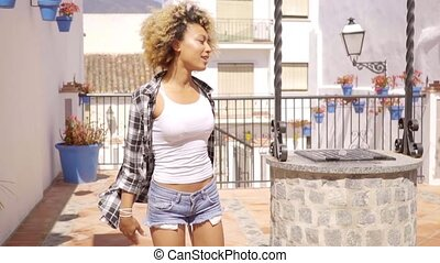 Young Woman in Plaid Shirt Walking in Sunshine
