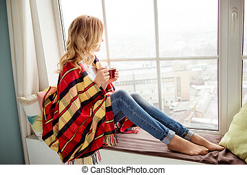 Young woman in plaid with cup of hot tea sitting on windowsill