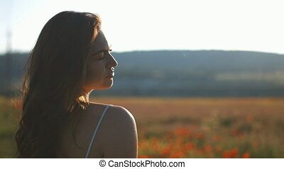 Young woman in poppy field touching flowers at sunset