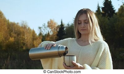 Young woman in pouring hot tea with steam from thermos to...