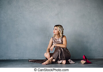 young woman in purple dress sitting on a floor