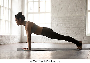Young woman in Push ups or press ups pose, studio - Young...