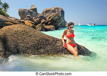 Young woman in red bikini sitting on huge rock in a nice turquoise sea. Similan islands, Thailand