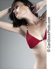 Young woman in red bikini top