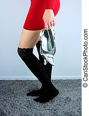 Young woman in red dress and black stockings holding in hand high heel shoes.