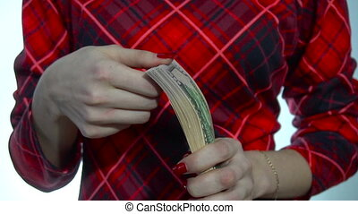 young woman in red dress counts a pack of money in hands in slow motion