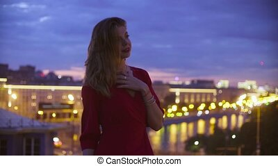 Young woman in red dress is standing near parapet